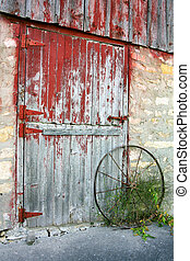 a rustic old barn door with peeling red paint, stone walls, and a rusted antique wagon wheel