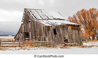 Rustic old farmers barn in the winter with full moon in the sky