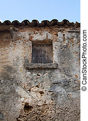 Rustic old wooden hatch on stone building with tiled roof