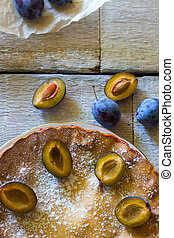 rustic plum cake on white wooden background.