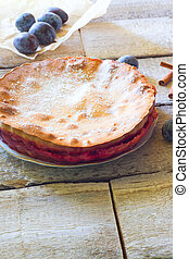 rustic plum cake with knife and fork on white wooden background.