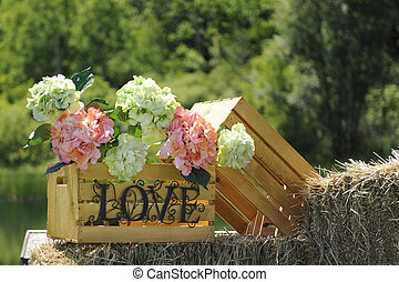 Close-up image wooden crate full of flowers atop bales of straw and surrounded by summer foliage.