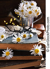 rustic style still life with old books and daisy flowers on wooden table