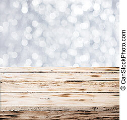 Close-up of a rustic table made of wooden planks with shiny blurred snowflakes falling in the background, in winter