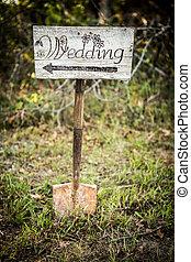 Rustic wedding arrow sign on a shovel.