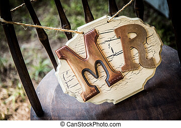 Rustic wedding sign sitting on a chair.