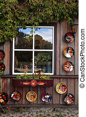 rustic window with ceramic plates and flower pot in wood rural house