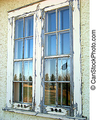 Rustic windowpanes in an abandoned building reflect the country side.