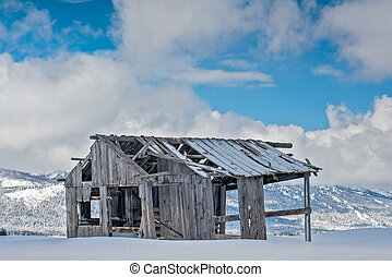 Rustic winter barn rotting in the snow mountains