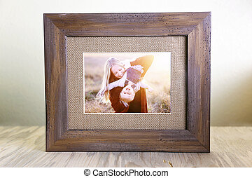 Rustic Wood Framed Portrait of a Mother and Her Baby Playing Outside at Sunset