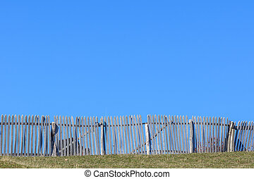 Rustic wooden fence around cows and clear blue sky. Beautiful sunny autumn mountain view with rustic fence, grass and blue sky background.