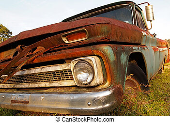 Extreme closeup of an old, vintage truck rusting away in a grassy field.