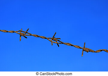 rusty barbed wire against deep blue sky