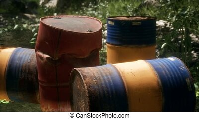 Rusty barrels in green forest illustrates the pollution of environment by oil spills