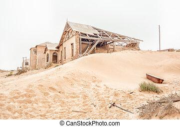 Rusty bathtub and ruins on a dune at Kolmanskop