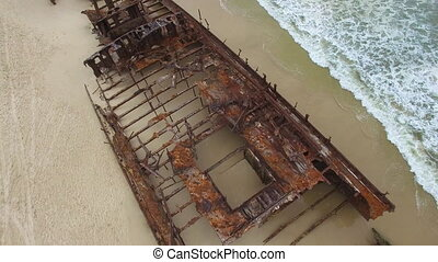 Rusty boat on shore with waves