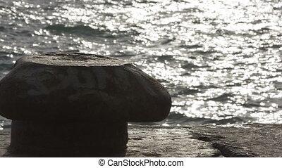 Rusty bollard on pier - Old pier with a rusty bollard, surf...