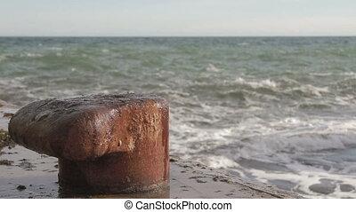 Rusty bollard on pier - Old pier with a rusty bollard, with...