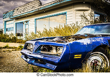 Rusty and damaged car sitting outside an old abandoned gas station.