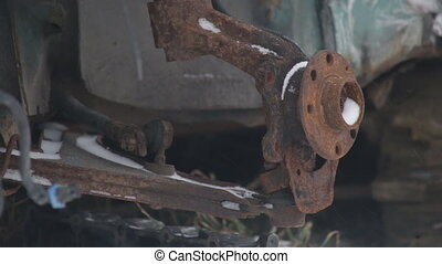 rusty car parts in the dump, close-up, winter