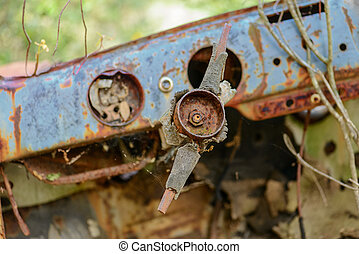 Rusty car wreck abandoned in a wood. Rusty details of the...