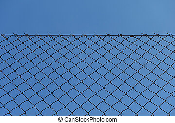 rusty chain link fence and blue sky background