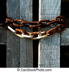 Rusty chains on wood - Rusted chains holding an old door