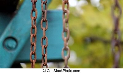 Rusty chains swayed gently