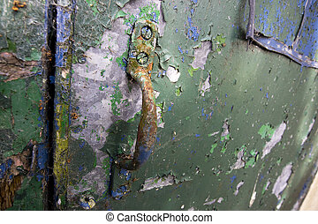 Rusty corroded door handle on dilapidated metal door with flaking paintwork with shallow depth of field