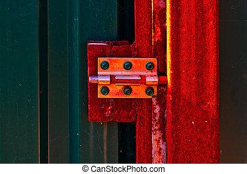 Rusty door hinge on metal door.