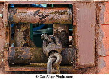 rusty fairlead with anchor chain at a ship hull