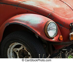 The front end of an old, dented, rusty Volkswagen Beetle