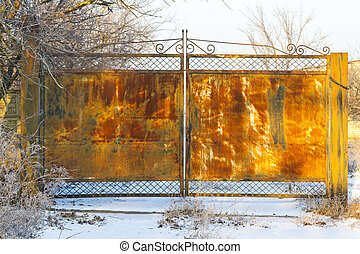rusty gate in the winter landscape , winter texture