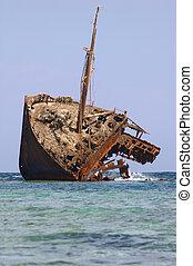 rusty half of an old ship run aground