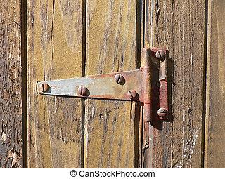 A rusty hinge on a weathered barn door.
