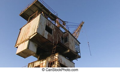 Rusty house with a crane - A full shot of a crane and a...