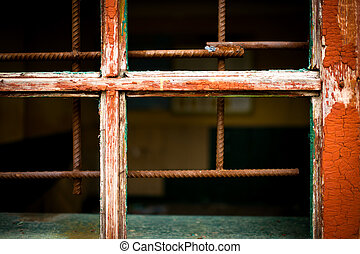 Rusty iron grid instead of window on a grunge background