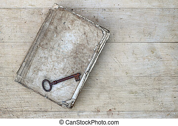 Rusty key on the old tattered book