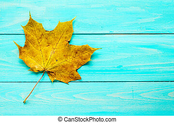 Rusty leaf over blue wooden background