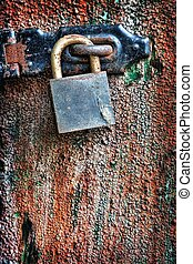 Rusty lock on wooden door - Old rusty padlock hanging on the...