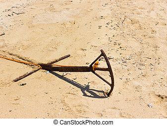 Rusty metal anchor on sand beach