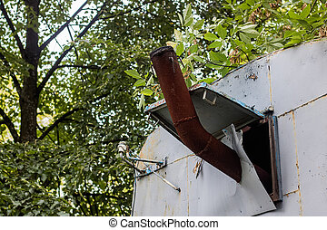 Rusty metal chimney on a background of green leaves on tree branches