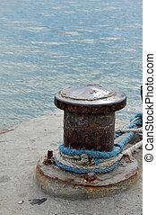 Rusty mooring bollard with ship ropes on seaport