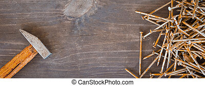 Rusty nails and an old hammer on the wooden background, banner