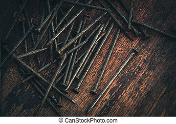 Rusty nails macro on the wooden background, toned