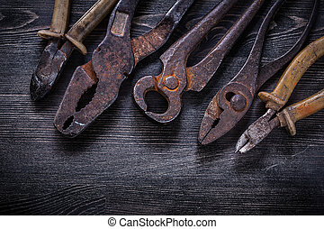 Rusty nippers pliers tin snips wire-cutter on wooden board.