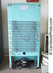 Rusty old cooling unit on the rear of a refridgerator