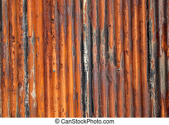 Rusty old corrugated iron fence close up.