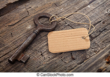 Rusty old key with a tag on wooden surface