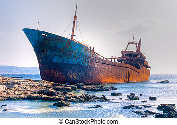 Rusty old shipwreck aground on rocky reef